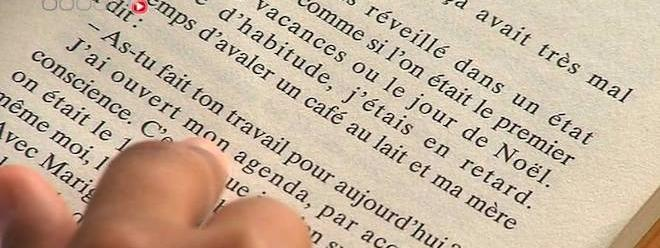 Gros plan sur une page avec une main qui aide à la lecture