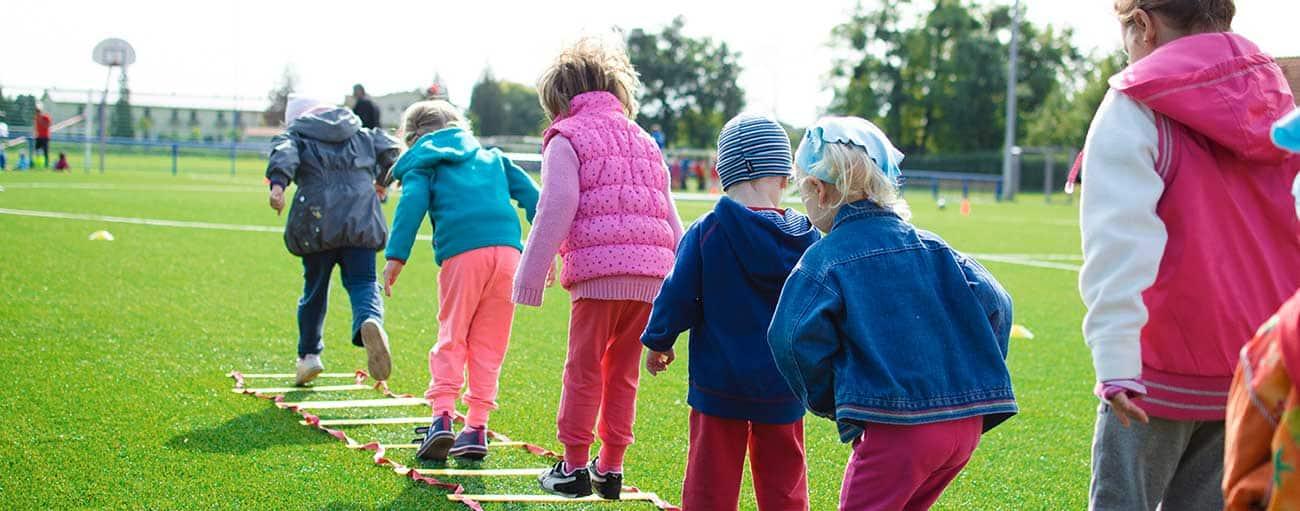 Enfants sur un terrain de sport faisant un exercice de motricité IME