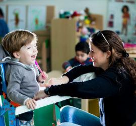 Enfant en fauteuil avec une personne adulte qui vieille à bien l'installer