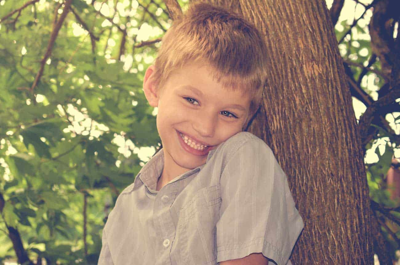 Autisme et scolarisation : Enfant autiste appuyé contre un arbre qui sourit