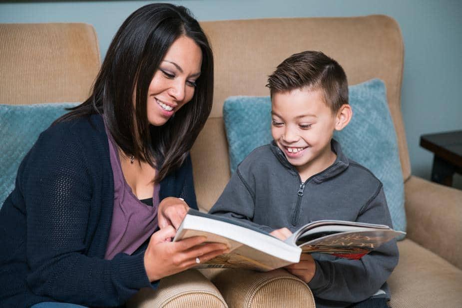 Un accompagnant AVS ou AESH qui aide un enfant à lire