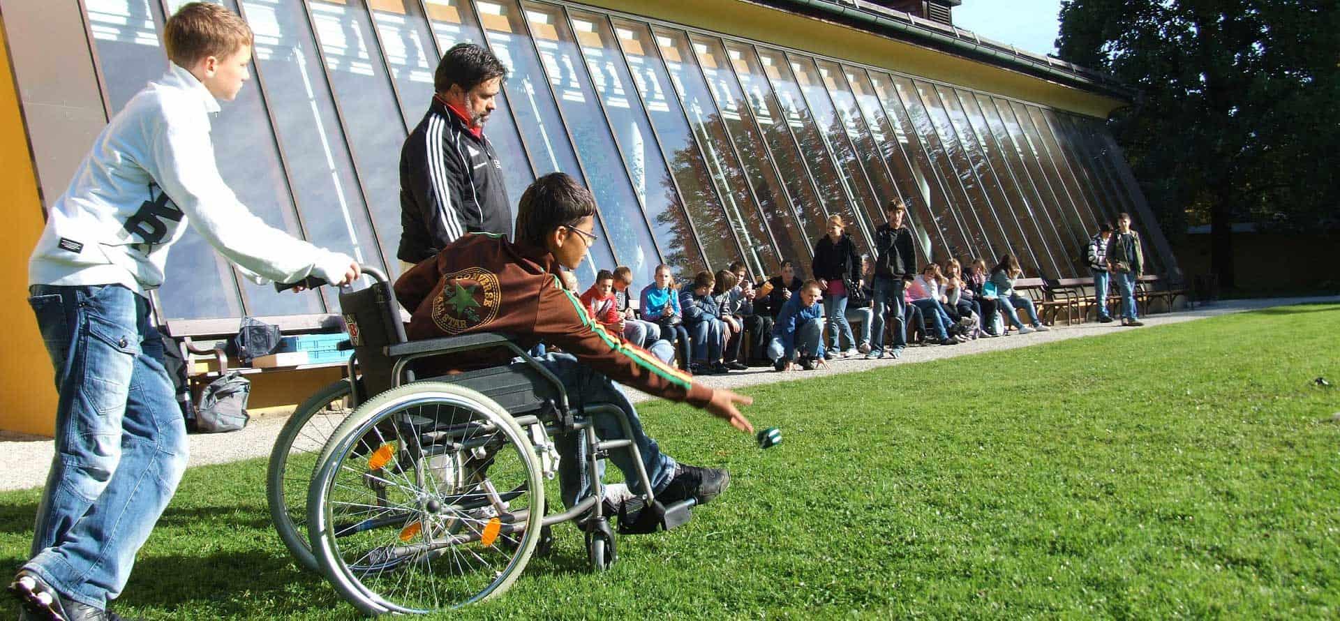 Personne poussant un enfant en fauteuil roulant dans une cours d'école