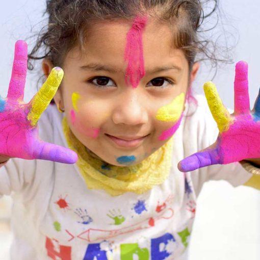 Petite fille avec les mains peintes en couleur qui sourit